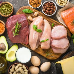 Protein sources. Meat, fish, eggs, cheese, milk, nuts, greens oil beans and lentils Top view on dark stone table